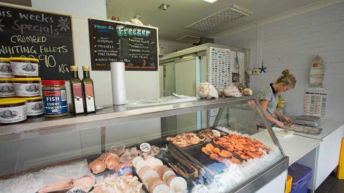 EASTER FEAST: Staff member Taya prepares a tray for display at Woolgoolga Aussie Fresh Seafood ahead of Good Friday.