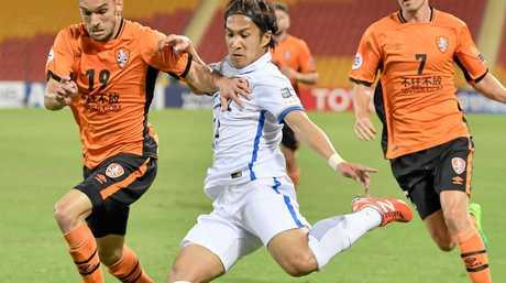 Jack Hingert (19) of the Brisbane Roar tries to block a kick from Takeshi Kanamori of Japan's Kashima Antlers