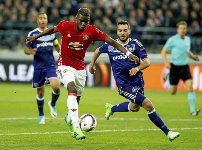 Manchester United's Paul Pogba is tracked by the Anderlecht defence.