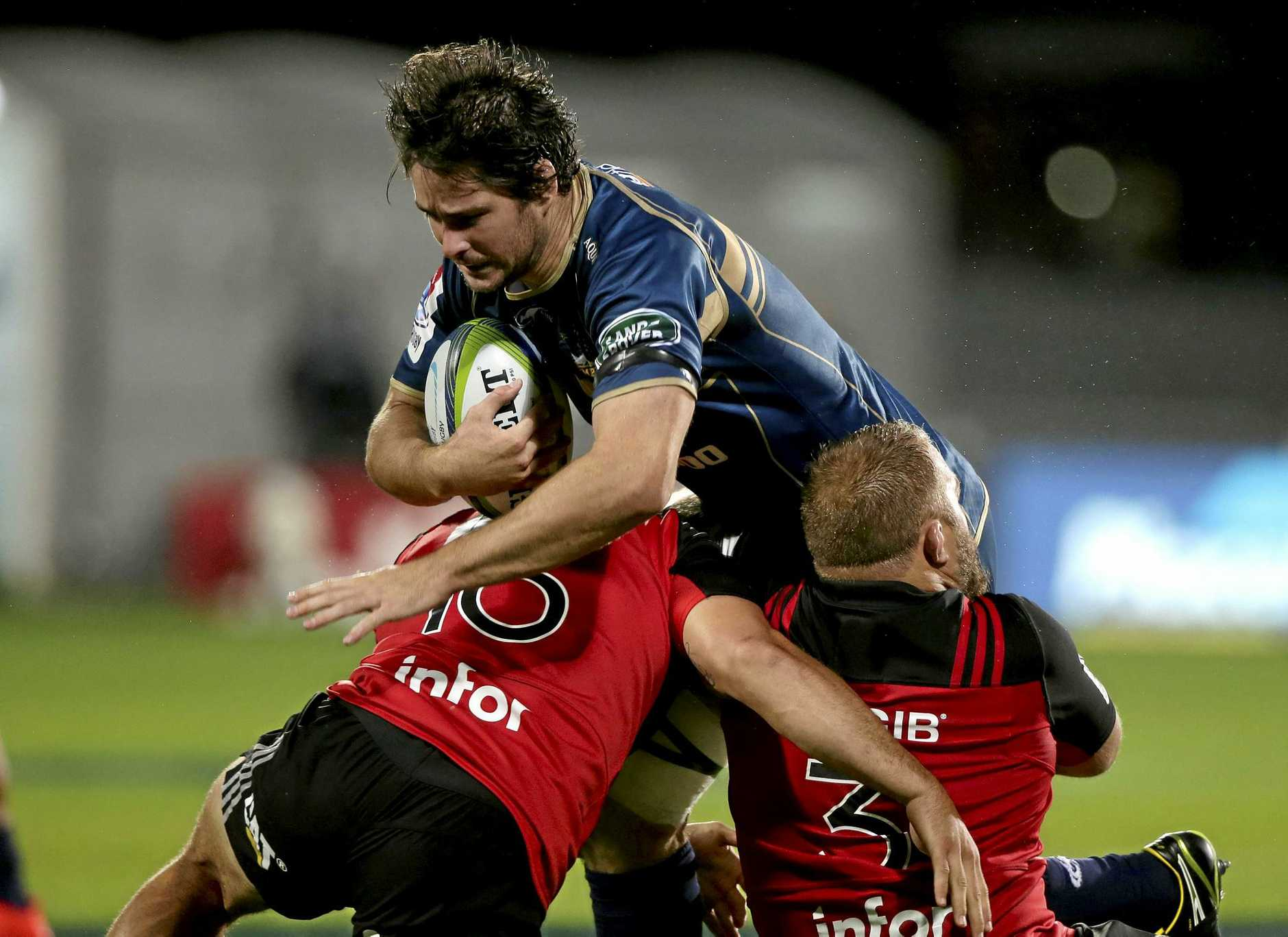 Brumbies player Sam Carter attempts to bust the tackle of Crusaders Codie Taylor and Owen Franks.