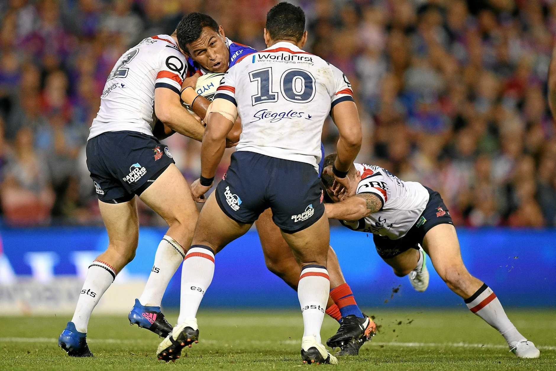 Daniel Safiti of the Knights is tackled by Mitchell Aubusson (left), Issac Liu and Paul Carter of the Roosters.