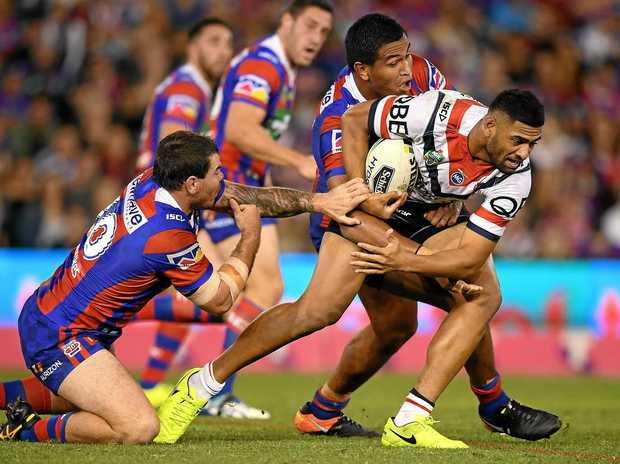 Daniel Tupou of the Roosters is tackled by Josh Starling (left) and Daniel Safiti of the Knights.