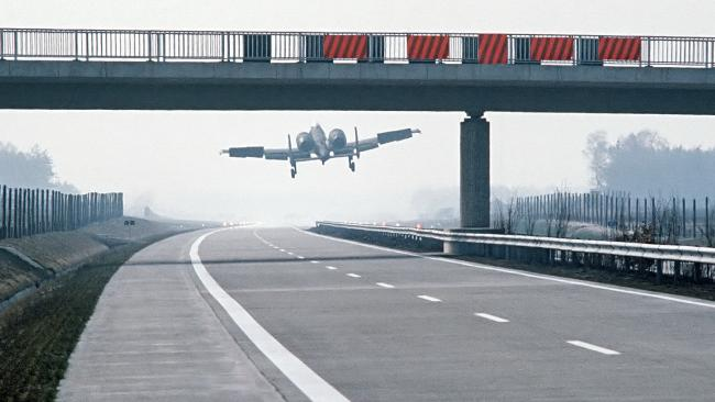 An A-10 Thunderbolt II aircraft lands on a German autobahn in the 1980s just past an overpass.