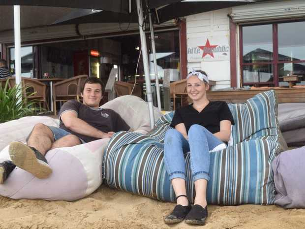 CLOSING SALE: Enzo's employees Tyson Stephens and Sherilyn Hogan relaxing on the cafe's famous bean bags.