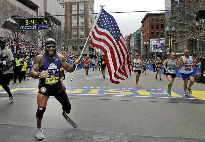 Jose Sanchez, of San Antonio, carries the American flag across the finish line in the 121st Boston Marathon