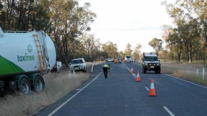A police officer at work at the scene of the crash near the intersection of the Leichhardt Hwy and Fairy Meadow Rd, south of Miles earlier today.