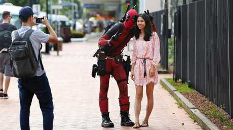 Stefanie Chueng poses with a man dressed as the comic book character Deadpool as her friend Joe Chen takes a photograph on his phone.