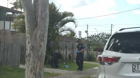 Police inspect a piece of blue cloth on Frank Street Morayfield, believed to be connected to the armed robbery at the nearby Spar convenience store.