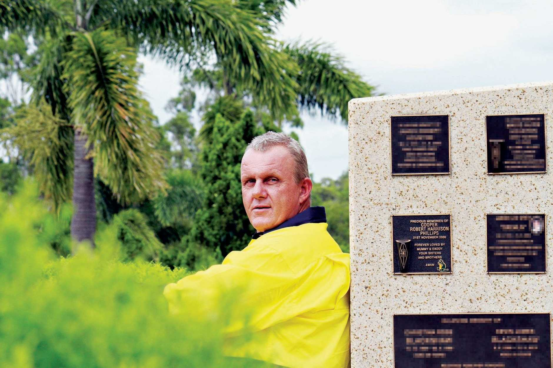 Robert Phillips sits next to the memorial for his son who died at birth. Mr Phillips works at the Albany Creek Memorial Park over-seeing cremations and burials.
