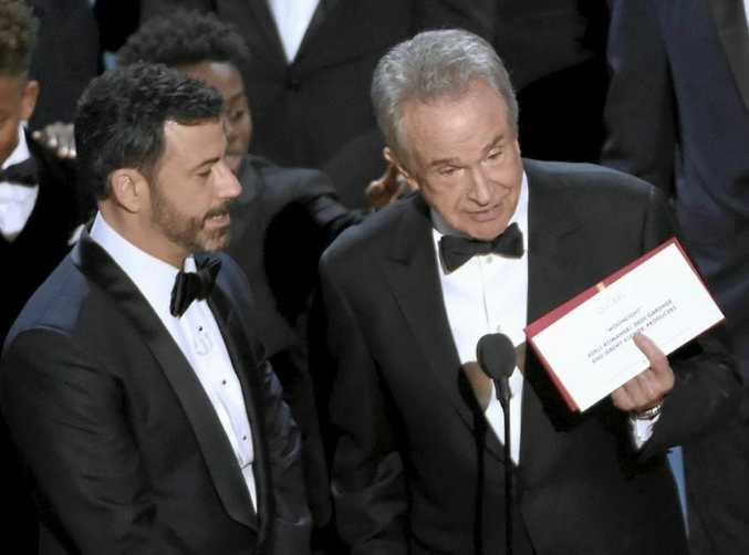 Presenter Warren Beatty shows the envelope with the actual winner for best picture, Moonlight as host Jimmy Kimmel look on at the Oscars in February.