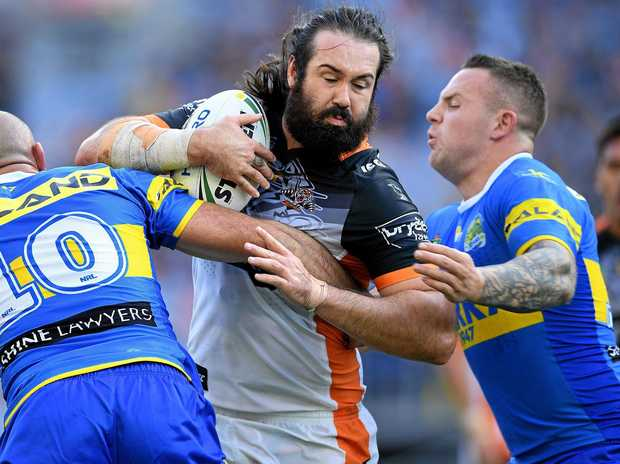 Aaron Woods of the Tigers is tackled by Tim Mannah (left) and Nathan Brown of the Eels.