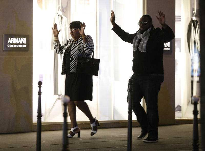 Bystanders raise their arms after a shooting in Paris.