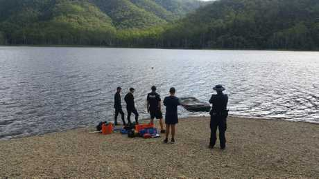 MYSTERY: Police from Imbil and the dive squad watch a car containing human remains pulled out of Borumba Dam yesterday.