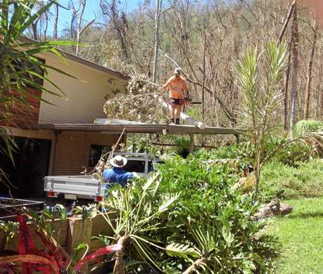 Ricky Falzon clears a fallen tree from the roof of Carmel Pyatt's house after Cyclone Debbie.