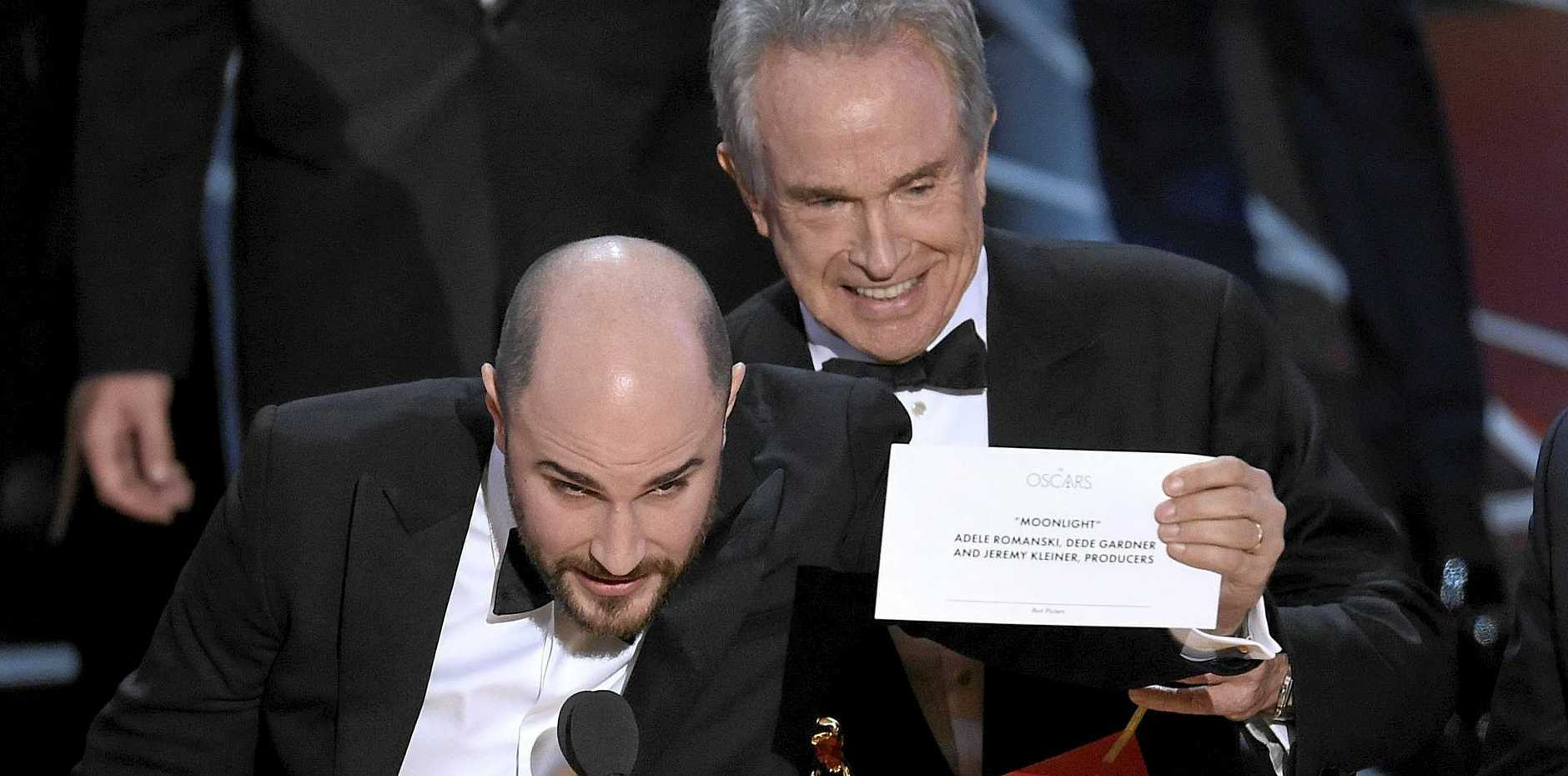 Jordan Horowitz, producer of La La Land, shows the envelope revealing Moonlight as the true winner of best picture at the Oscars on Sunday, February 26, 2017, at the Dolby Theatre in Los Angeles. Presenter Warren Beatty looks on from right.