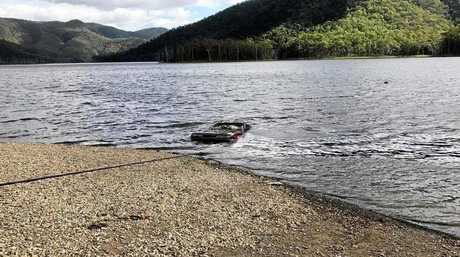 Clayton's Towing machinery dragged the car from Borumba Dam on Thursday afternoon before human remains were discovered inside.