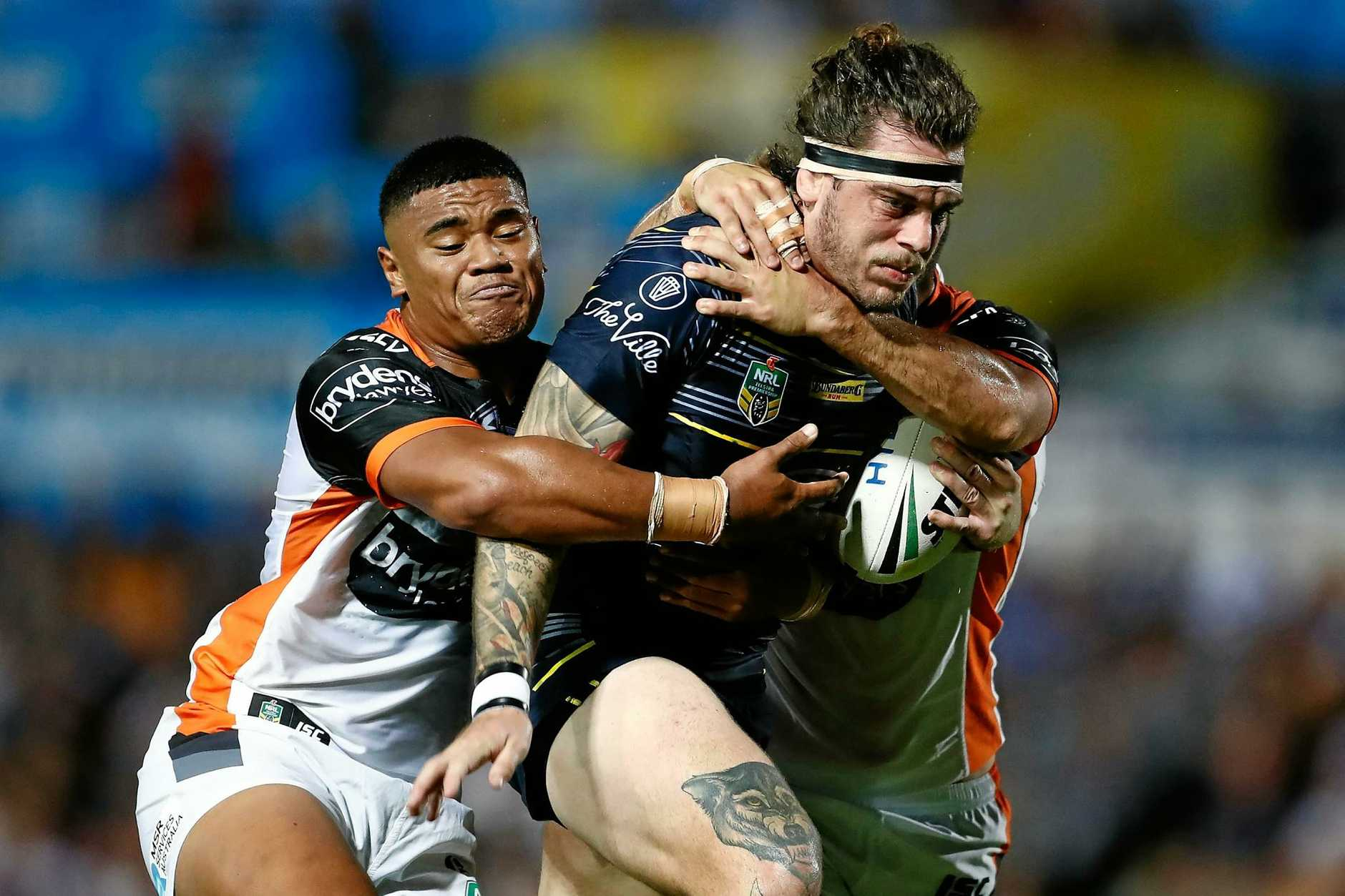 Ethan Lowe of the Cowboys is tackled by the Tigers defence last week.