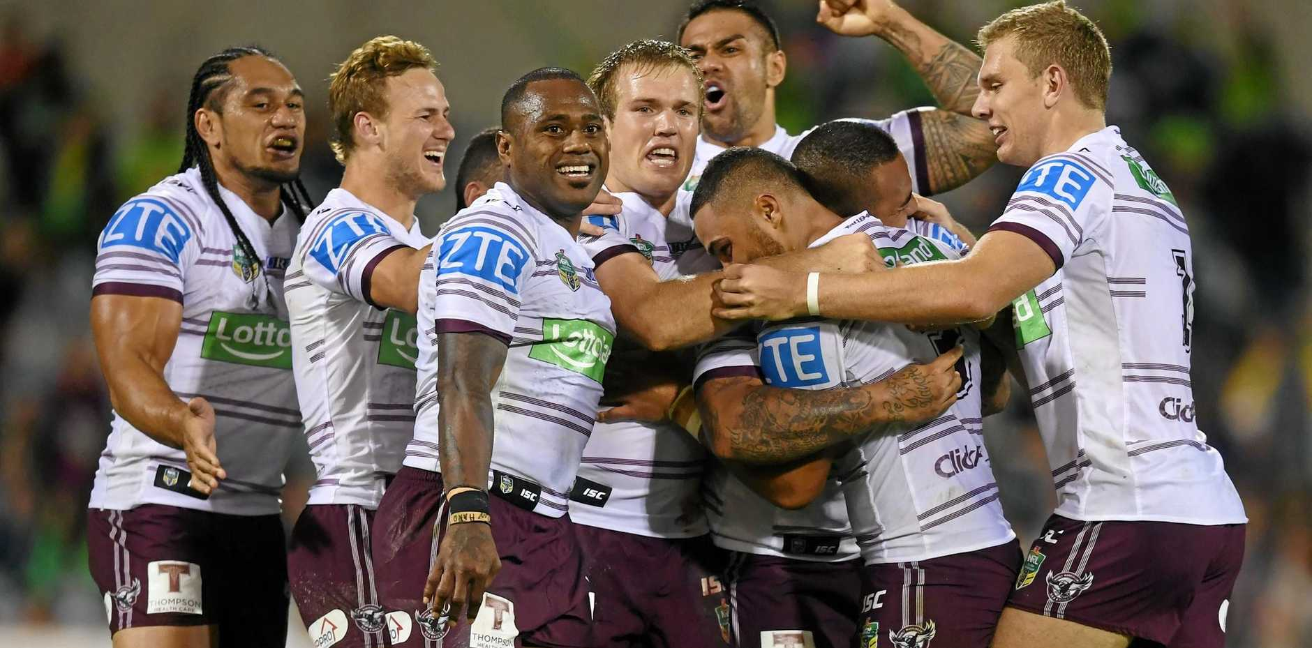 Dylan Walker of the Sea Eagles (centre) celebrates after scoring the winning goal against the Raiders.