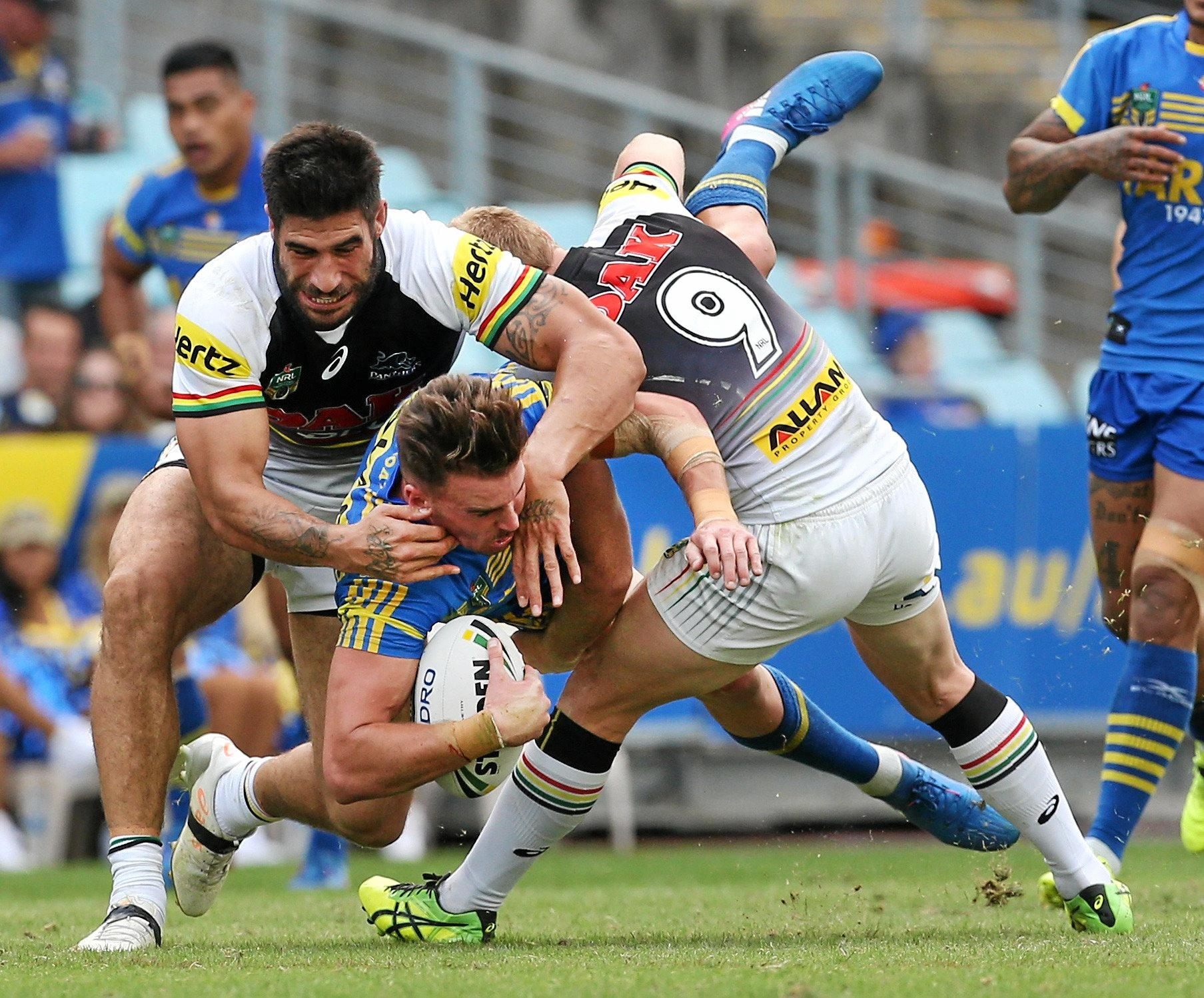 Clinton Gutherson of the Eels is tackled by James Tamou and Peter Wallace of the Panthers.