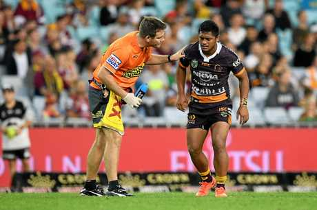 Anthony Milford of the Broncos receives attention from a trainer after a late shoulder charge from George Burgess of the Rabbitohs.