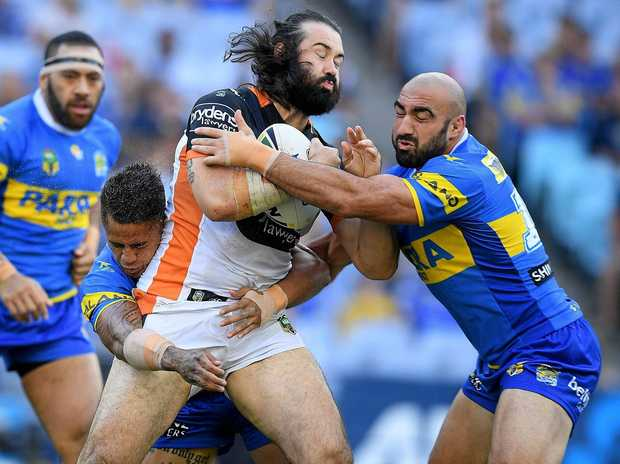 Aaron Woods of the Tigers is tackled by Kaysa Pritchard (left) and Tim Mannah of the Eels.