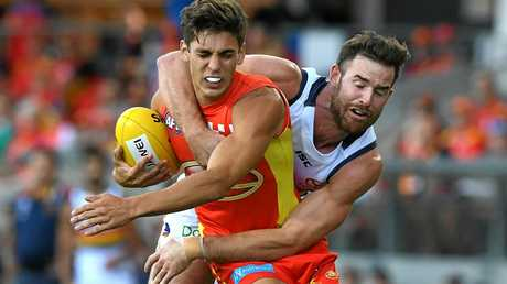 Suns player Sean Lemmens (left) competes with Crows player Andy Otten.