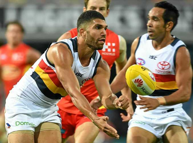 Crows player Curtly Hampton get a handball away.