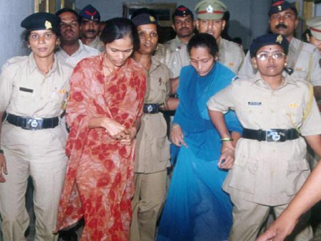 Officers escort Seema Mohan Gavit (red sari) and Renuka Shinde to an appeal hearing.