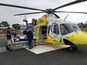 HORSE FALL: Airborne paramedics prepare to airlift a woman to Brisbane after she was injured in a fall from a horse at the Manumbar Campdraft on Saturday.