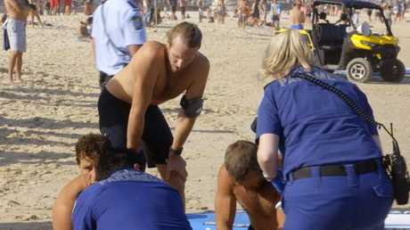 Bondi Rescue's Wally Eggleton leans over to catch his breath as Corey Oliver, right, continues to work on the unconscious Norwegian man.