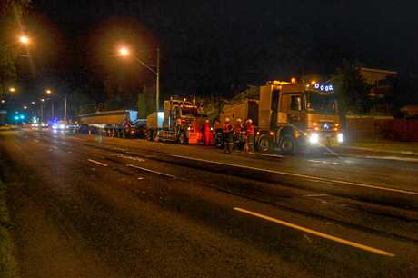 TRUCKING UP THE RANGE: Workers gather around the front of the convoy to detach the trucks once they reach the top of the Toowoomba range, at 4am on the Friday morning.