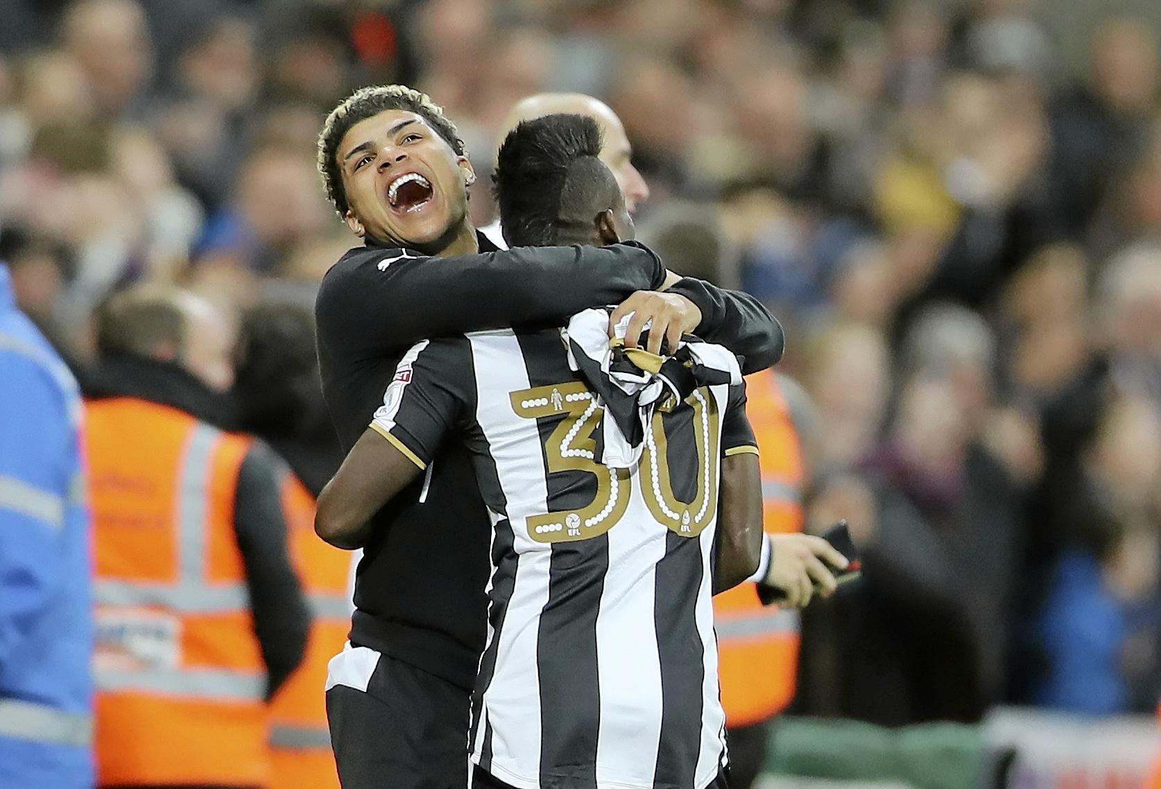 Newcastle United's Christian Atsu (right) celebrates promotion with a clubmate.