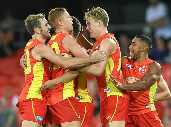 Gold Coast Suns players celebrate scoring a goal against the Brisbane Lions in their round one game at Metricon Stadium.