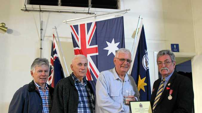 Peter Sheedy (left), Terry Sheedy and Barry Sheedy accept a certificate of honour on behalf of their father, Bryan, from Marian RSL sub-branch president John Edwards.