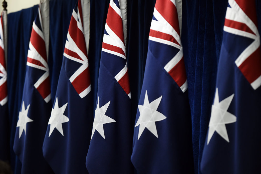 A collection of Australian flags are lined up prior to a press conference after the Council of Australian Governments (COAG) meeting held in Sydney, Thursday, July 23, 2015. (AAP Image/Dean Lewins) NO ARCHIVING