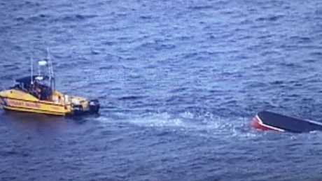 An overturned vessel under tow from a Coast Guard boat off North Stradbroke Island. Picture: Nine News Queensland