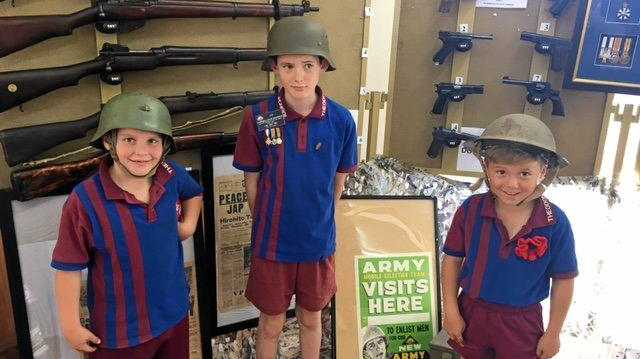 YOUNG RECRUITS: Xavier Bugg, Harry Anderson and Warick Dale try on helmets from around the world. Harry offered his expertise on the display, correctly naming most of the firearms.