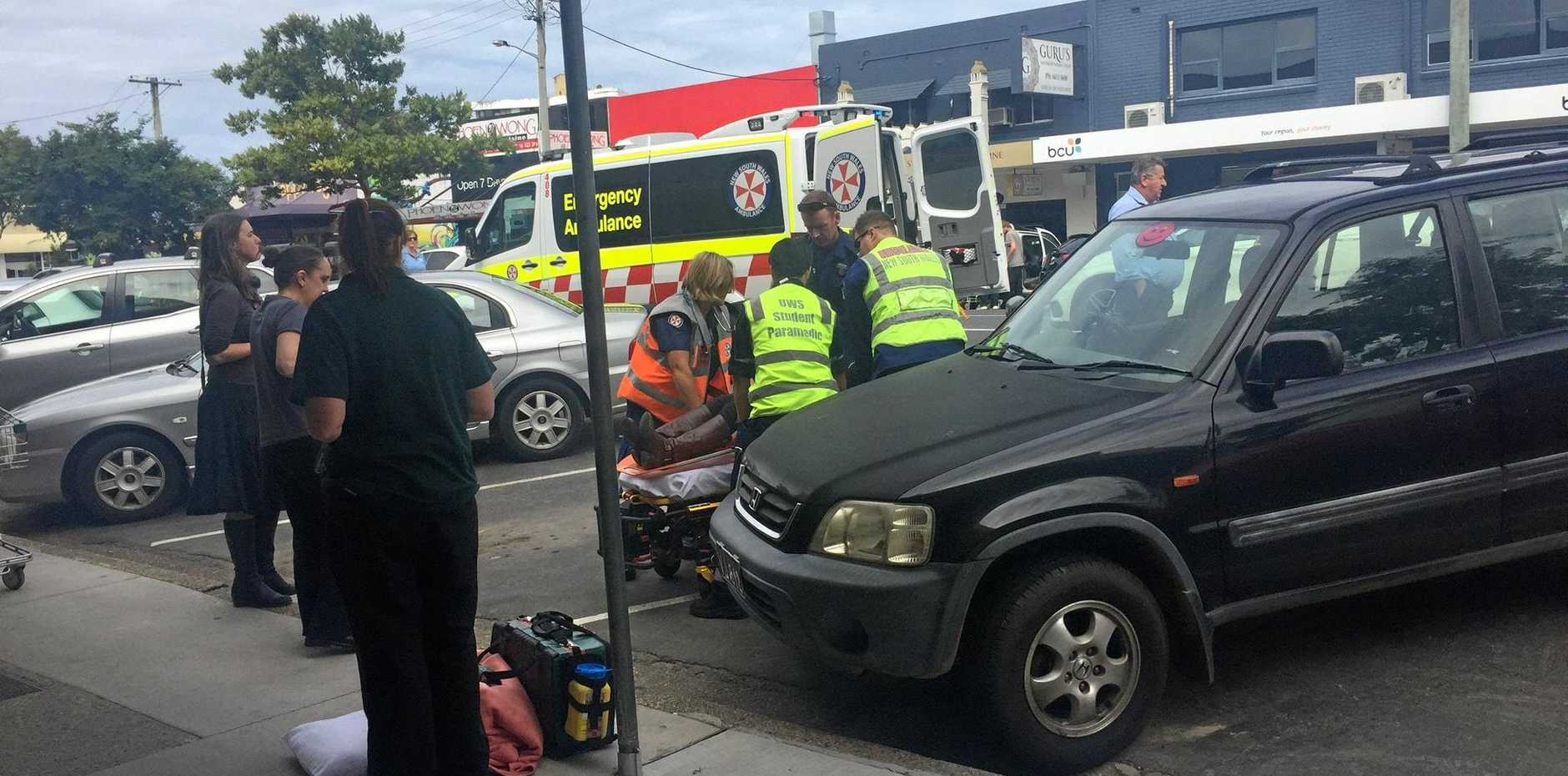 Paramedics treat a woman who was struck by a vehicle while crossing the road in Park Ave.