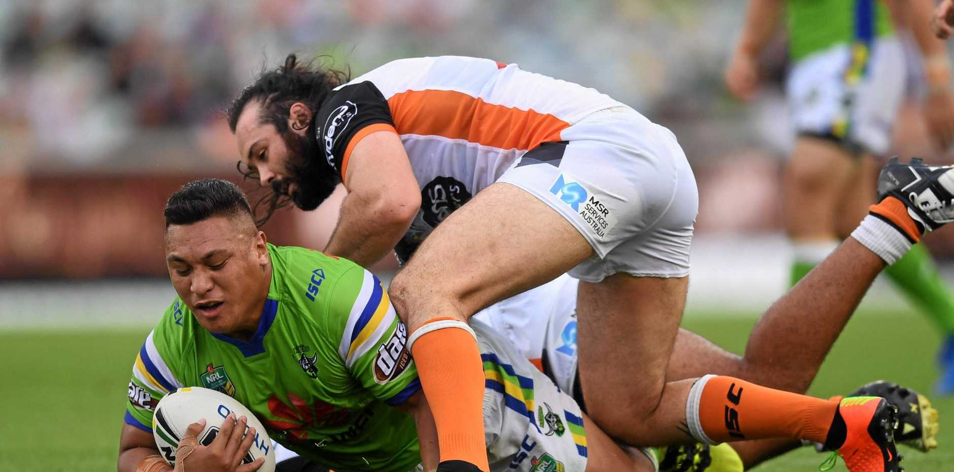 Josh Papalii of the Raiders is tackled by Aaron Woods of the Tigers.