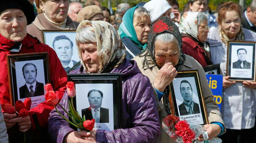 Widows of Ukrainian men involved in the clean-up at Chernobyl display portraits of their husbands near a monument in Kiev.