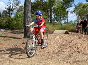 CRUISING: Ma Ma Creek student Teejay puts his new skills into practice on the schools new bike track, followed by Jakobi and bike coach Darren Rolf.