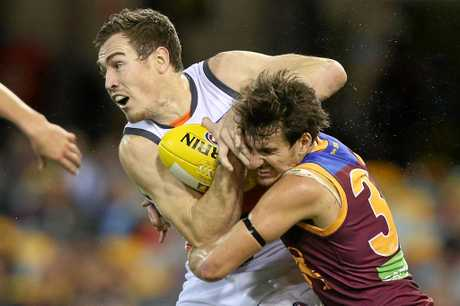 Jeremy Cameron of the Giants is tackled by Sam Mayes of the Lions.