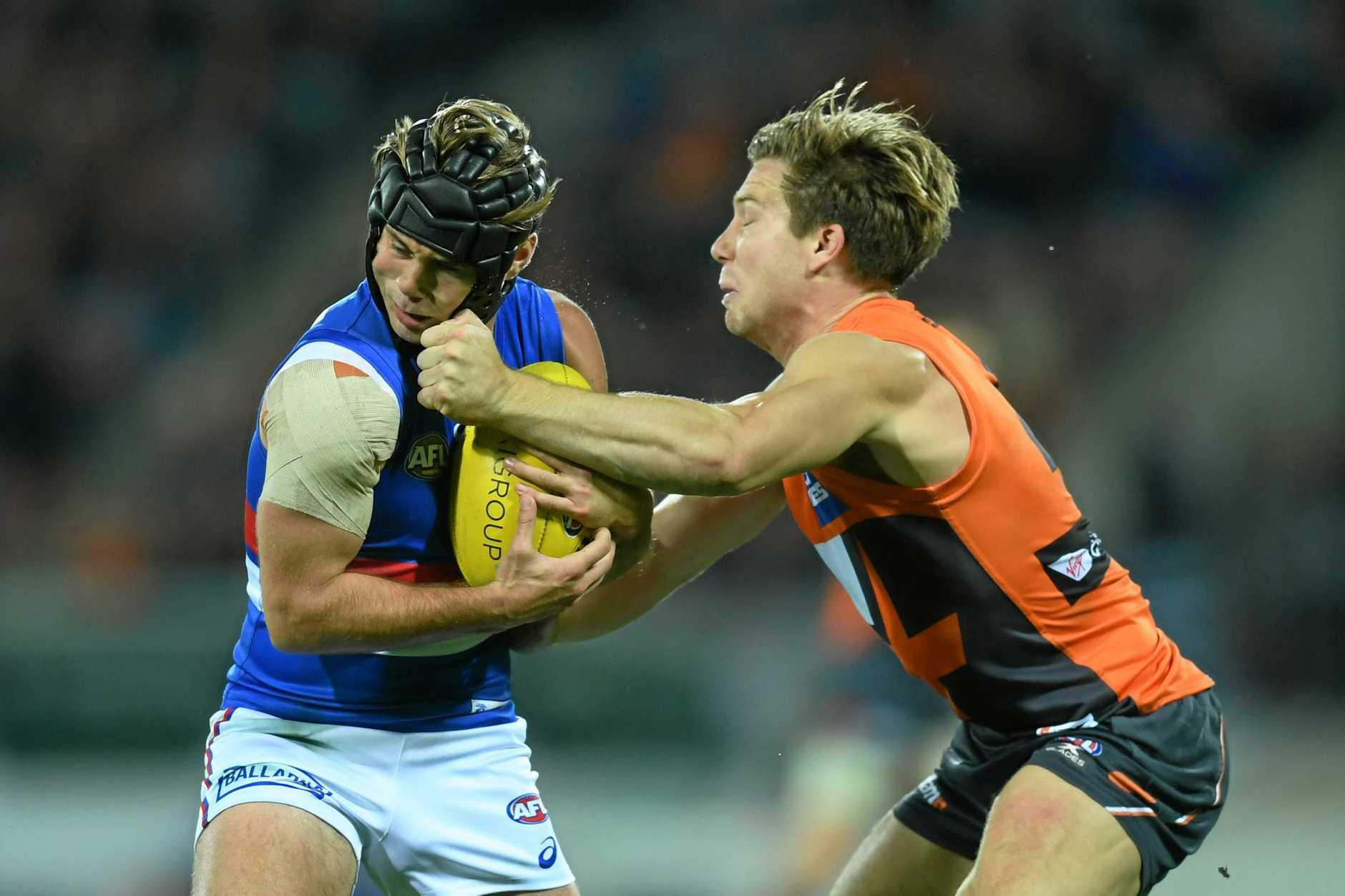 Toby Greene of the Giants (right) puts a shot on Caleb Daniel of the Bulldogs.