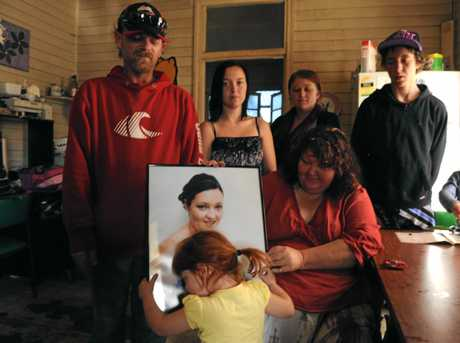 MISSING YOU: Rebecca's daughter Rylee Ely hugs the photograph of her mother as the family look on back in 2012. Warwick Ely, Tianna Ely, Ashleigh Kitching-Ely and Trent Ely and in front Debbie Sutton.
