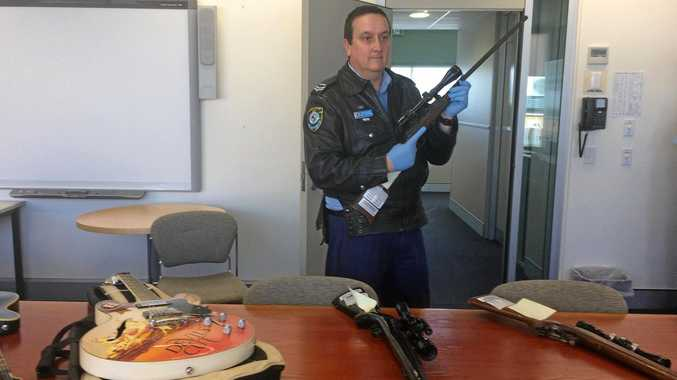 Snr constable David Henderson with guns and guitars recovered from drug bust home.