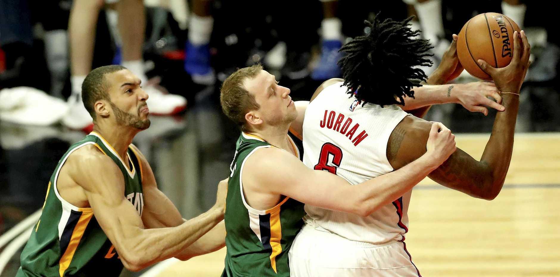 The LA Clippers' DeAndre Jordan (R) is tied up  by Utah Jazz's Joe Ingles