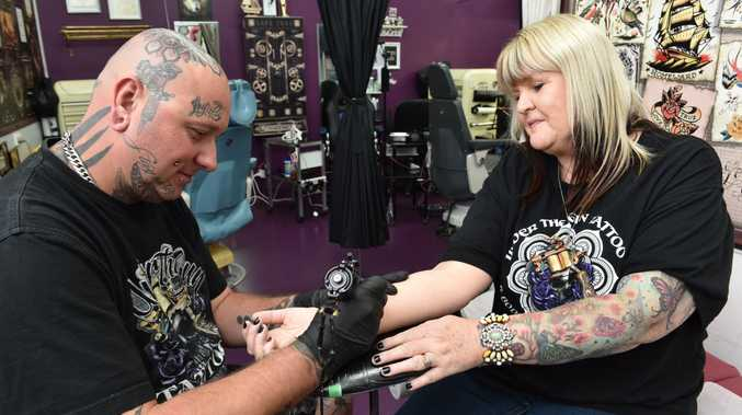 Shirlee Faint from Maryborough getting a tattoo to show her support for cancer research. Pictured with tattooist Justin Stat.