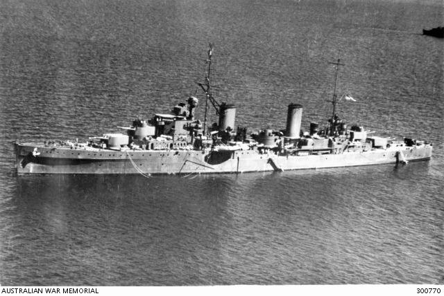 1943-06-08. AERIAL PORT SIDE VIEW OF THE CRUISER HMAS HOBART (I). THE HOBART IS PAINTED IN A CAMOUFLAGE SCHEME OF ALL OVER DARK GREY (G10). THE CLOSE RANGE ARMAMENT HAS BEEN STRENGTHENED WITH 20 MM OERLIKON AA GUNS NOTICEABLE ON B AND X TURRETS, IMMEDIATELY BEFORE THE BRIDGE AND IN THE AFTER SUPERSTRUCTURE. THERE IS A QUADRUPLE 2 POUNDER AA MOUNTING ON THE QUARTERDECK. TYPE 271 SURFACE SEARCH RADAR IS FITTED BETWEEN THE AFTER FUNNEL AND THE MAINMAST, SC-1 AIR SEARCH RADAR AT THE HEAD OF THE FOREMAST AND TYPE 284 FIRE CONTROL RADAR TO THE MAIN ARMAMENT DIRECTOR. NOTE THE PARAVANES ON THE DECK NEAR B TURRET. (NAVAL HISTORICAL COLLECTION)