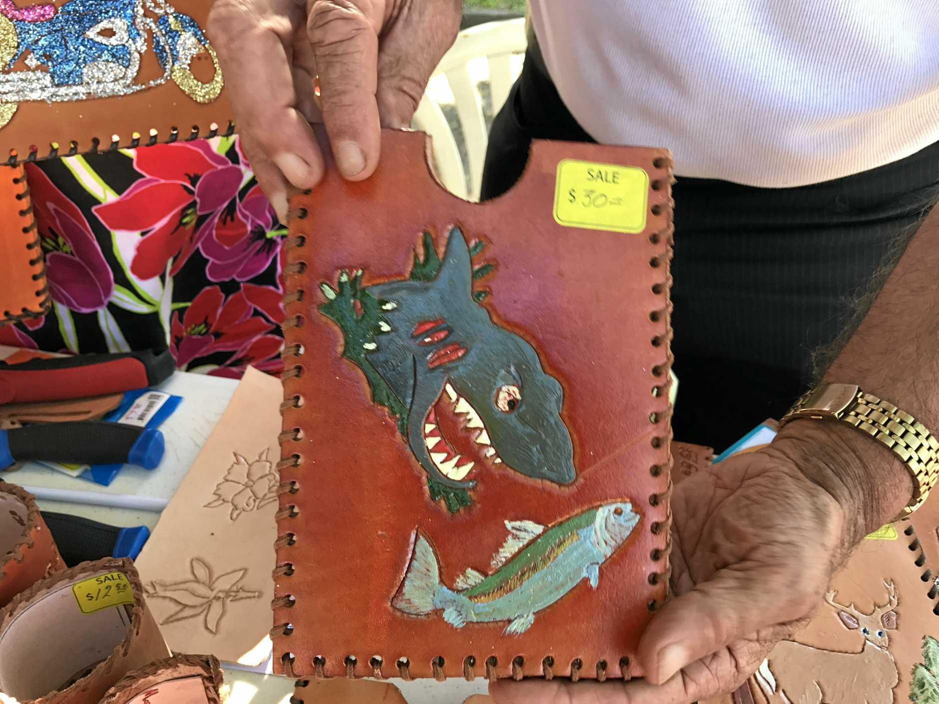 A tablet holder that tells a story, Peter Grabyn says on one side it shows a fisherman, and on the other side, a shark going after the fish.