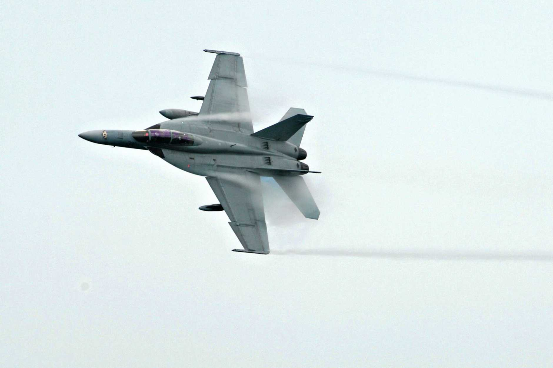 An F/A-18F flying over Point Danger in 2016